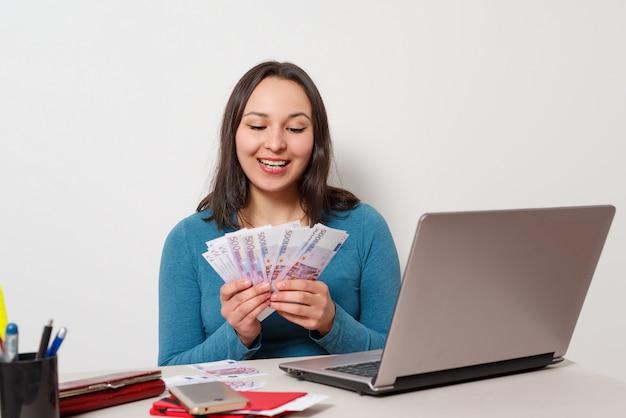 Молодая жизнерадостная женщина, держащая вентилятор наличных денег банкноты, сидеть и работать на стол с ноутбуком на белой стене