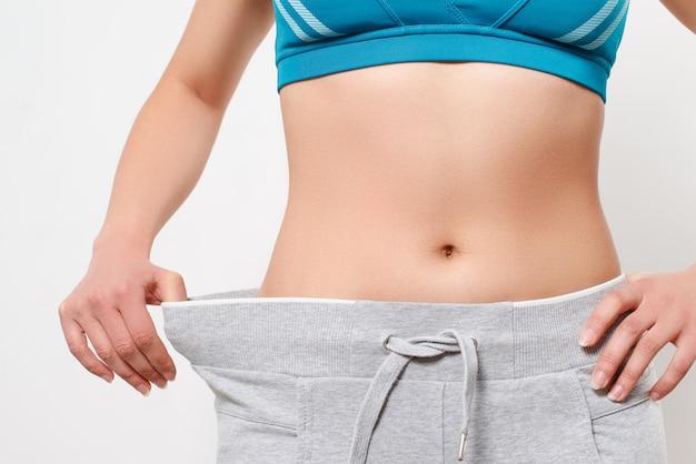 Худая девушка в больших штанах. концепция потери веса.