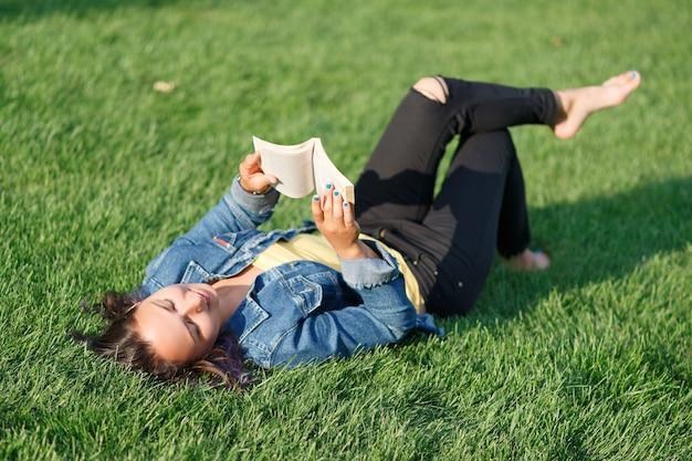 Молодая женщина, лежа на зеленой лужайке в парке летом и почитать книгу