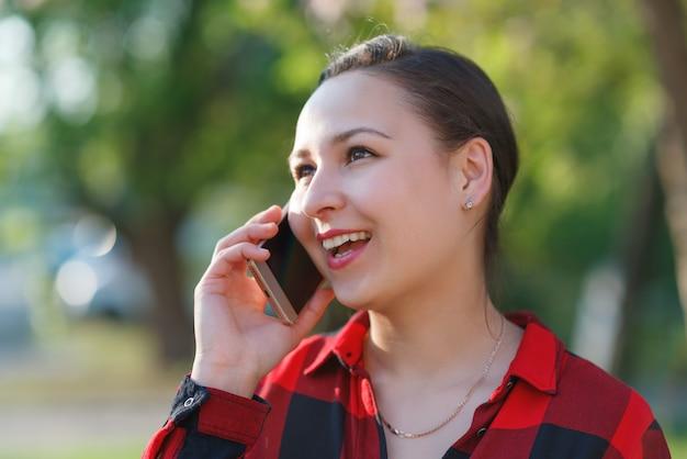 スマートフォンを手に持った、幸せな若いブルネットの女性の肖像画。女性の携帯電話で話していると笑顔します。晴れた日に撮影