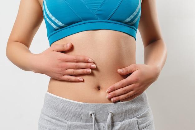 妊娠初期、適切な栄養、女性の健康の概念。ほっそりした美しい腹と女性のへそのクローズアップ写真。彼女は両手のひらを腰に当てます