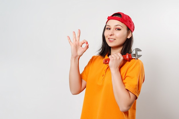 Портрет молодой женщины с гаечным ключом в руке.