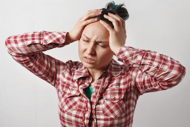 若い女の子が両手で頭をつかみ、激しい頭痛を描いています。均一な灰色の空間