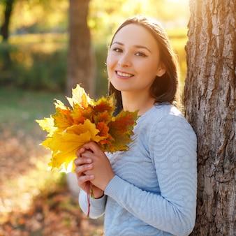 紅葉の前に葉を持つ秋の笑顔の若い女性の肖像画