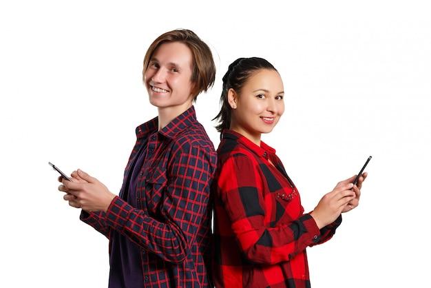Парень и женщина стоят спиной к спине и держат смартфон на белой стене