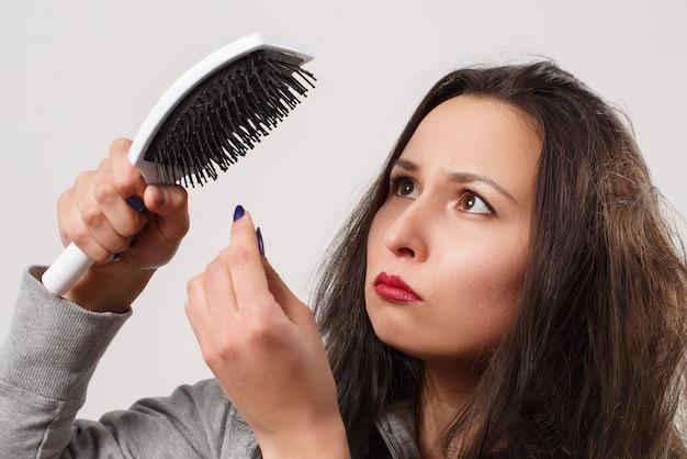 Женщина с растрепанными лохматыми волосами держит в руках расческу