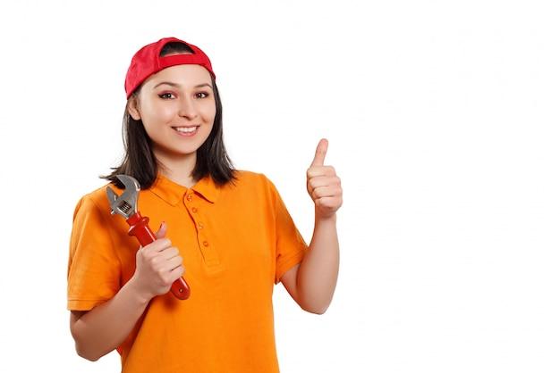 Портрет молодой женщины с гаечным ключом в руке. на белой стене