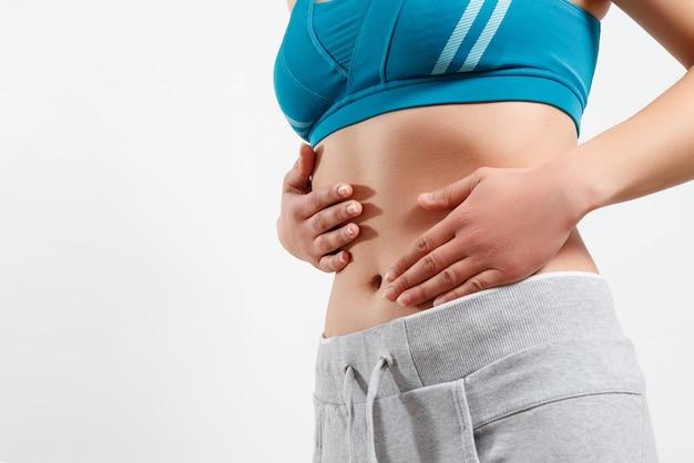 妊娠初期、適切な栄養、女性の健康の概念。細長い美しい腹と女性のおへそのクローズアップ写真。彼女は両手で腰に触れます