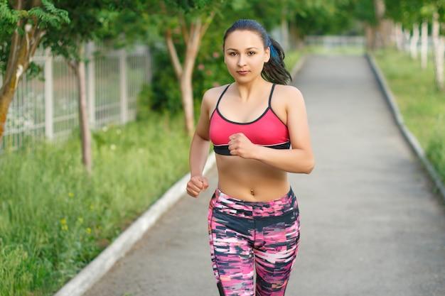 走っている女性。公園での屋外トレーニング中にジョギングする女性ランナー。美しいフィット女性。屋外フィットネスモデル。
