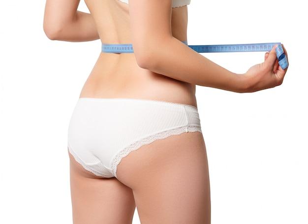 スリムな女性が彼女の腰を測定します。白い壁に分離されました。背面図