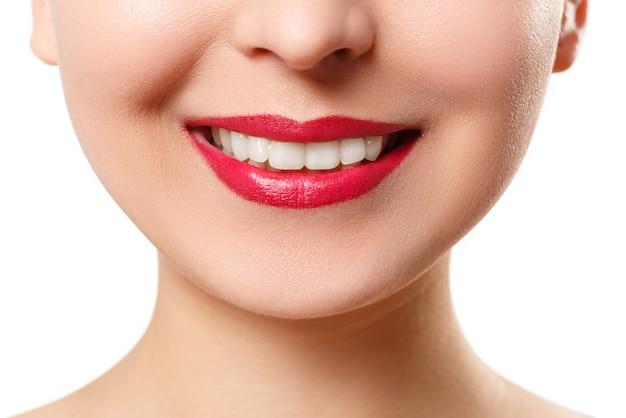 完璧な白い歯を持つ若い女性の笑顔。白で隔離されるクローズアップ