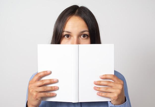 Молодая женщина держит перед ней книгу и выглядывает из-за нее