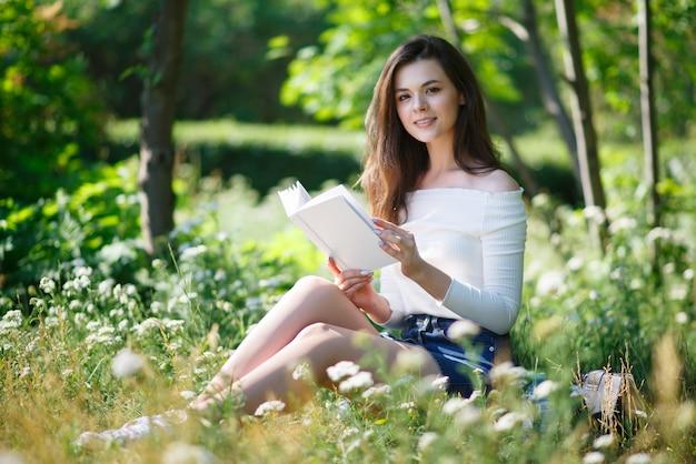 美しい少女は、屋外の夏の公園で本を読みます。