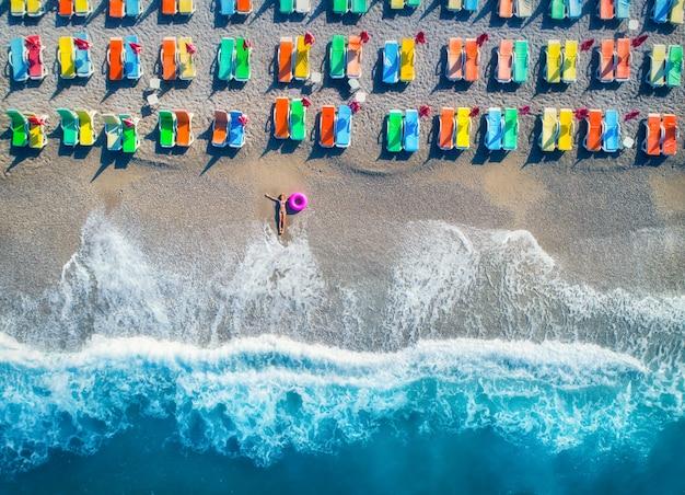 海で泳ぐリングで横になっている女性の空撮