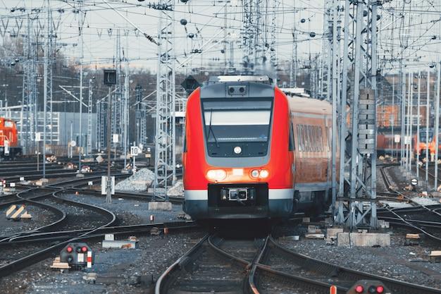 Железнодорожный вокзал с современным красным пригородным поездом на закате