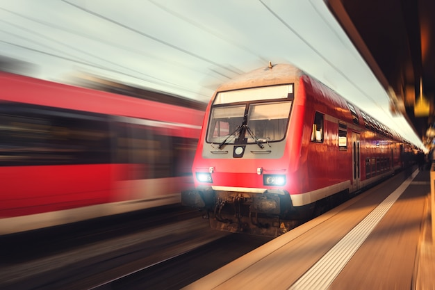 Красивый железнодорожный вокзал с современным красным пригородным поездом на закате