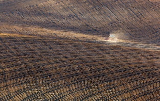 裸の畑を耕すトラクター