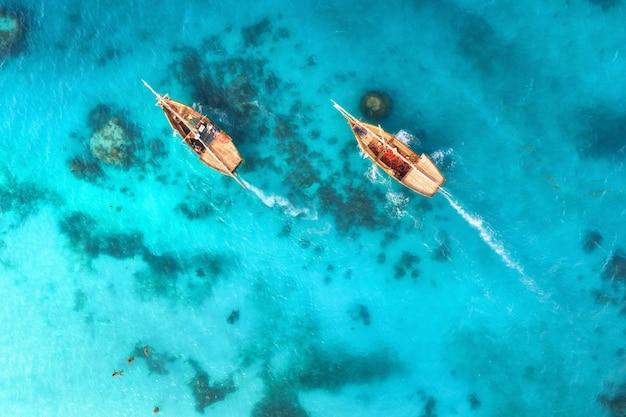 夏の夕暮れ時の澄んだ青い水の漁船の空撮