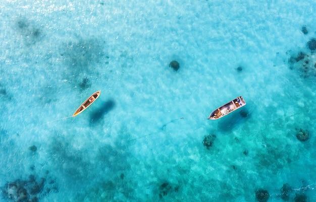 夏の晴れた日に澄んだ青い水の漁船の空撮