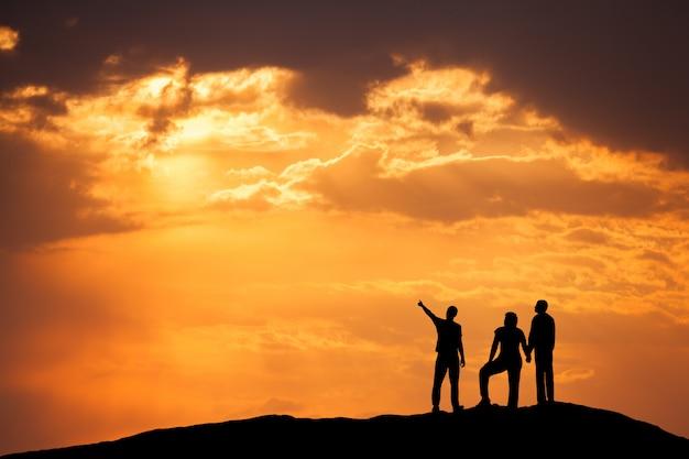 夕暮れ時の山に幸せな人々のシルエットのある風景します。