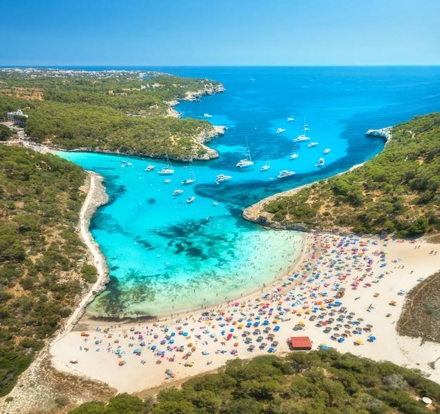Аэрофотоснимок песчаного пляжа, синего моря, людей и яхт