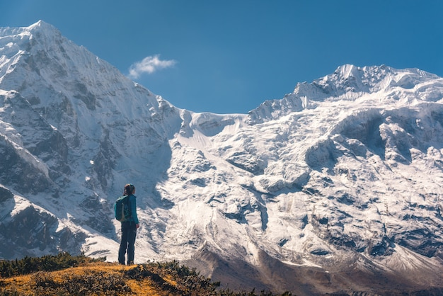 丘の上に若い女性に立って、素晴らしいヒマラヤ山脈を探して