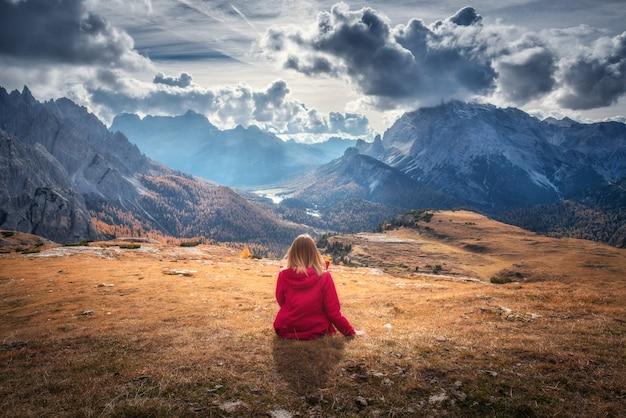 若い女性は秋の夕暮れ時の雄大な山々に対して丘の上に座っています。