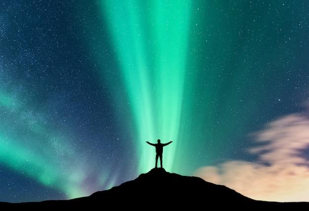 オーロラと山の上に腕を上げると立っている男のシルエット