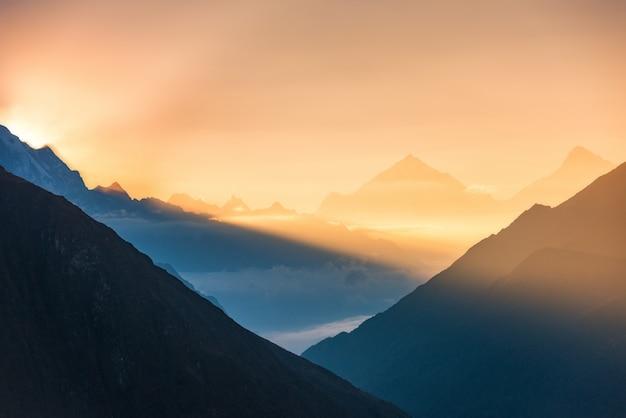ネパールのカラフルな日の出で山と低い雲