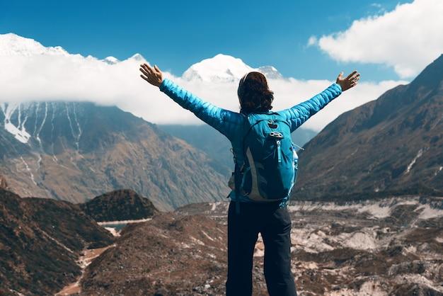 Стоящая молодая женщина с рюкзаком и поднятыми вверх руками на холме и глядя на горы