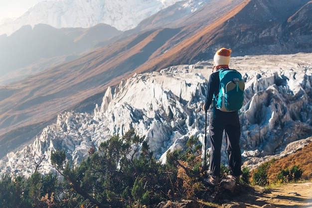 山のピークにバックパックを持つ若い女性に立って、美しい山々と日没の氷河を探して