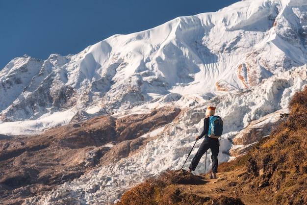 Стоящая молодая женщина с рюкзаком на вершине горы и глядя на красивые горы и ледник на закате
