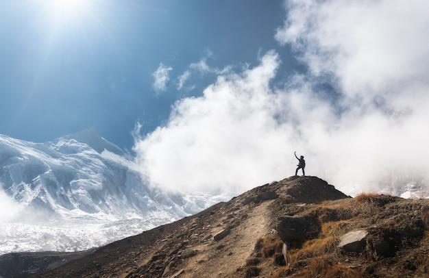 明るい日に低い雲と青い空を背景に山頂に腕を上げて立っている若い女性