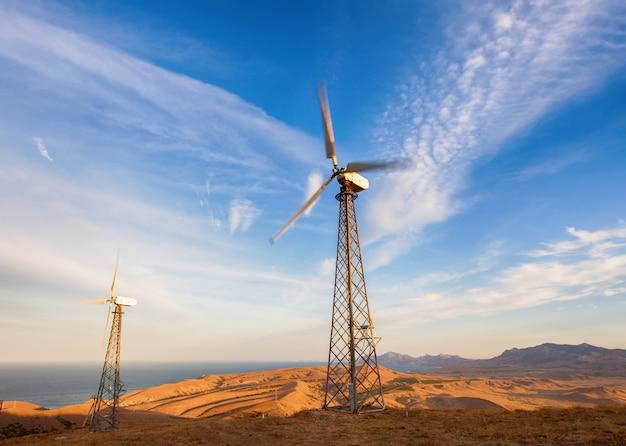 夕暮れ時の山で電気を生成する風力タービンの産業景観。