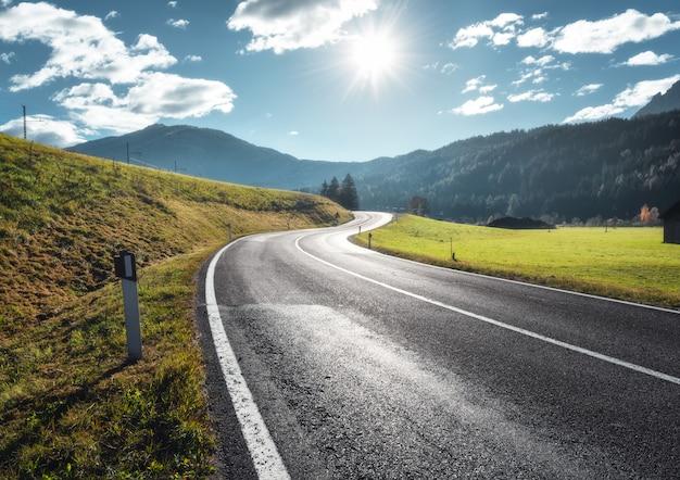 ドロミテ、イタリアの晴れた朝の山の谷の道。アスファルト道路、緑の草の牧草地、山、雲と太陽と青い空を表示します。フィールドの高速道路。ヨーロッパ旅行。トラベル
