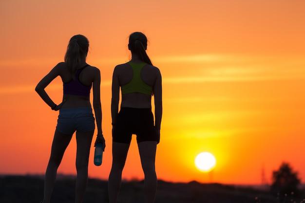 Пейзаж с силуэтом молодых спортивных девушек на закате
