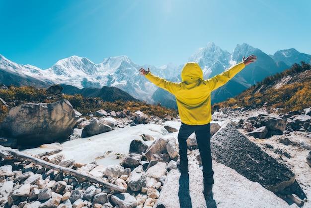 明るい日に雪に覆われた山々を見ている川の近くに腕を上げて立っている男。