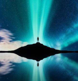 ノルウェーの丘に立つ男のオーロラとシルエット。オーロラと人間。星と緑の極光。