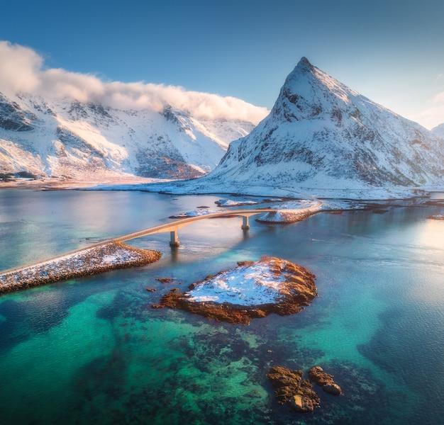 ロフォーテン諸島、ノルウェーの海と雪山に架かる橋の空撮。冬の夕暮れ時のフレドヴァング橋。