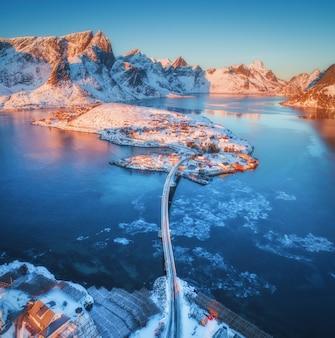 ロフォーテン諸島、ノルウェーの海と雪山に架かる橋の空撮。冬の日の出のレーヌとハムノイ。
