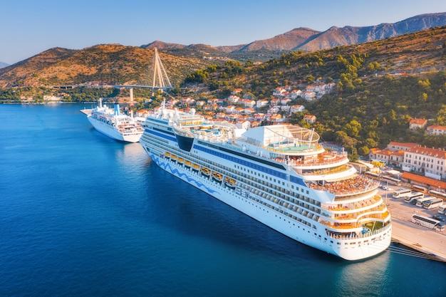 港のクルーズ船。日の出の美しい大型船やボートの空撮。港、都市、山、青い海でボートのある風景。