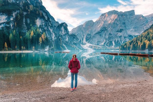 Женщина в красной куртке стоит на берегу озера браиес на рассвете осенью. доломиты, италия.