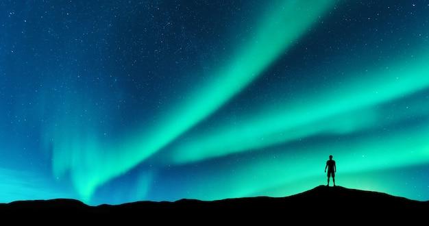 オーロラと丘の上に立っている一人の男のシルエット。ロフォーテン諸島、ノルウェー。オーロラと若い男。星と緑の極光の空。