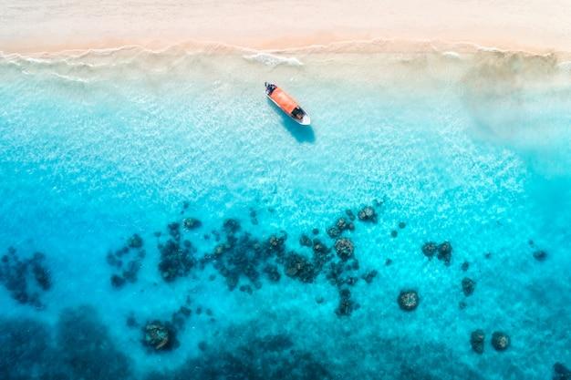 夕暮れ時の澄んだ青い水の中の漁船の空撮