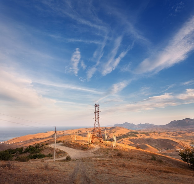 夕暮れ時の山の高電圧塔