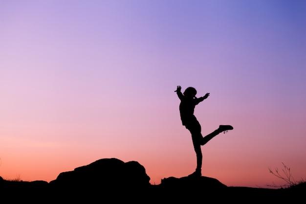 Силуэт счастливой молодой женщины против красивого неба захода солнца