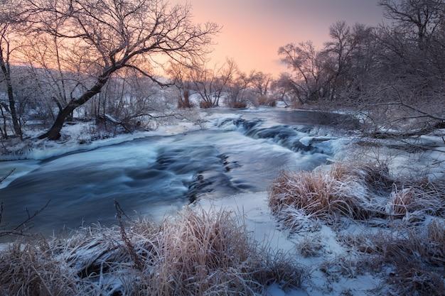 Зимний пейзаж со снежными деревьями, красивая замерзшая река на закате
