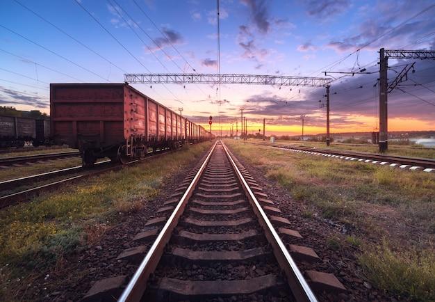 日没時の貨物列車プラットフォーム。ウクライナの鉄道。鉄道駅
