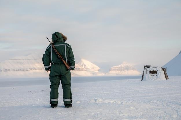 ライフルを持つ男は、スバールバル諸島の北極圏の風景の地平線に見えます
