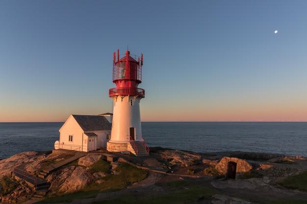 丸い窓から見たノルウェーの歴史的な灯台、リンデスネス・フィア
